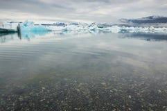 小卵石和清楚的水在著名冰盐水湖, Jokulsarlon, Icel 免版税库存照片