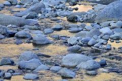 小卵石和鹅卵石蓝色冰砾在河床,水绘与日落光芒在金黄颜色,一个现代设计我 免版税库存照片