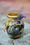小卵石和水在一个瓶子有花的在石头被弄脏的背景分支 库存照片