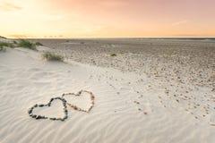 小卵石在两心脏形状安排了在沙子海滩波纹的与美好的日落 免版税库存图片