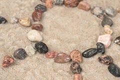 小卵石在沙子的太阳标志 免版税库存图片