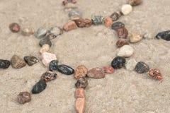 小卵石在沙子的太阳标志 库存照片