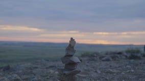 小卵石塔禅宗和平衡 小卵石的堆反对天空的 石头塔在领域的背景的和 免版税库存照片