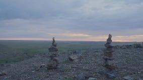 小卵石塔禅宗和平衡 小卵石的堆反对天空的 石头塔在领域的背景的和 免版税库存图片