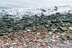 小卵石浇灌,河床小卵石,春天场面在水河岸,蓝色,红色和绿色下的特写镜头小卵石 免版税库存照片