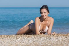 小卵石海滨的好少妇 免版税库存照片