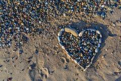 小卵石的心脏在金黄和软的沙子的在海滩 库存图片
