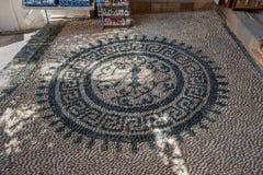 小卵石石头马赛克 罗塞达花卉主题 路面 Lindos镇 罗得岛希腊海岛  欧洲 免版税库存图片