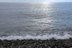 小卵石靠岸与波浪并且晒黑反射,蓝天,多云天气 免版税库存照片