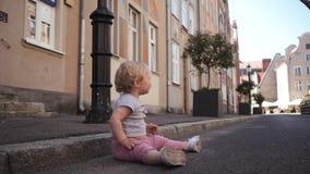 小卷曲白肤金发的女孩坐路旅行的步行沿着向下街道 影视素材