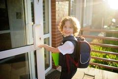 小卷毛男小学生打开学校门 免版税库存图片