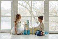 小可爱的坐在一个大窗口附近我的兄弟和姐妹 免版税库存图片