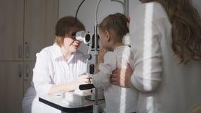 小可爱的女孩在儿童` s眼科学方面-检查眼力的验光师 库存照片