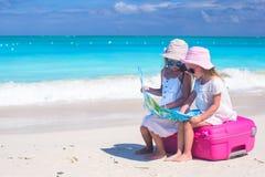 小可爱的女孩坐大手提箱和地图在热带海滩 免版税库存图片