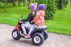 小可爱的姐妹坐自行车以绿色 图库摄影
