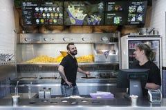 小吃店专门了研究获得的炸薯条和的职员乐趣 库存照片