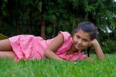 小吉普赛儿童女孩在草微笑的愉快放置在旁边穿衣 免版税图库摄影