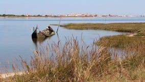 小和剥落凹下去的小船在出海口半淹没了,包围由植被 天际的小古雅镇 影视素材