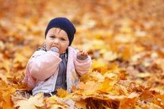 小哀伤的女孩在秋天公园 免版税库存图片
