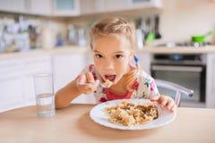 小哀伤的女孩坐在桌上并且吃肉饭 免版税库存图片
