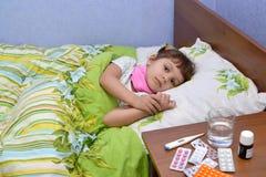 小哀伤的病的女孩在床上在 图库摄影