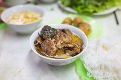 小圆面包查家,烤猪肉和米线越南著名汤面服务用新鲜的草本、调味汁和春卷 免版税库存照片