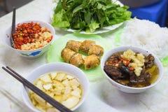 小圆面包查家,烤猪肉和米线越南著名汤面服务用新鲜的草本、调味汁和春卷 库存照片