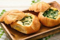 小圆面包烘烤了用鸡蛋和火腿在白色木桌上 免版税库存照片