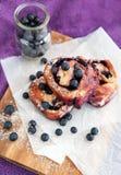 小圆面包用在紫色背景的蓝莓 图库摄影