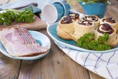 小圆面包用烟肉和新鲜的草本午餐的 蓝色盘 木背景和自由空间文本的 库存图片