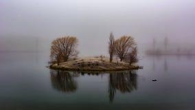 小土地的看法在湖中间的在有雾的da期间 库存图片