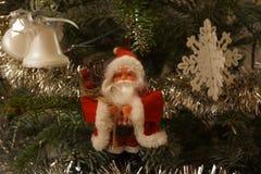 小圣诞老人在杉树垂悬了,在一个旁边有小响铃和在圣诞节另一边剥落  前面 库存照片