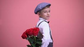 小在后面和转向的绅士孩子掩藏的玫瑰照相机后,微笑 影视素材