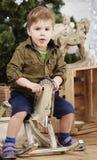 小在圣诞树前面的男孩乘驾木摇马 库存照片