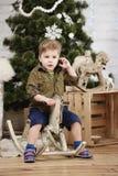 小在圣诞树前面的男孩乘驾木摇马 库存图片