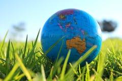小地球低角度在草的 旅行和全球性概念 免版税库存图片