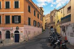 小型摩托车沿在城市的历史部分的狭窄的街道分开 免版税库存照片