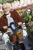 小型摩托车的老人在庭院 免版税库存图片