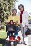 小型摩托车的资深妇女有朋友的 免版税库存照片