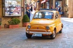 小城市汽车在街道上的菲亚特500在意大利 免版税图库摄影