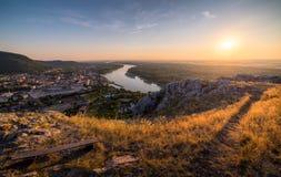小城市看法有河的从在日落的小山 免版税库存照片