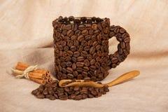 小堆咖啡豆,杯子,匙子,在粗麻布的桂皮枝 免版税库存照片