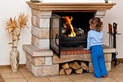 小壁炉的女孩温暖 免版税库存图片