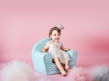 小女儿坐一把小孩似的扶手椅子 库存图片