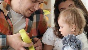 小女婴使用与坐在她的父母的塑料玩具接受慢动作 股票视频