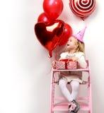 小女婴孩子庆祝她的与红色当前礼物和气球的生日 免版税库存图片