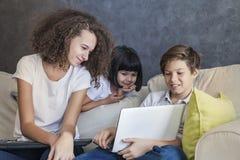 小女孩、青少年的男孩和卷发女孩wirh膝上型计算机在沙发a 免版税图库摄影