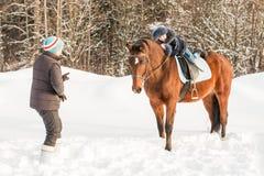 小女孩、驯马师和马在一个冬天 库存照片