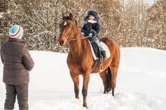 小女孩、驯马师和马在一个冬天 免版税库存照片