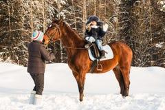 小女孩、驯马师和马在一个冬天 免版税库存图片